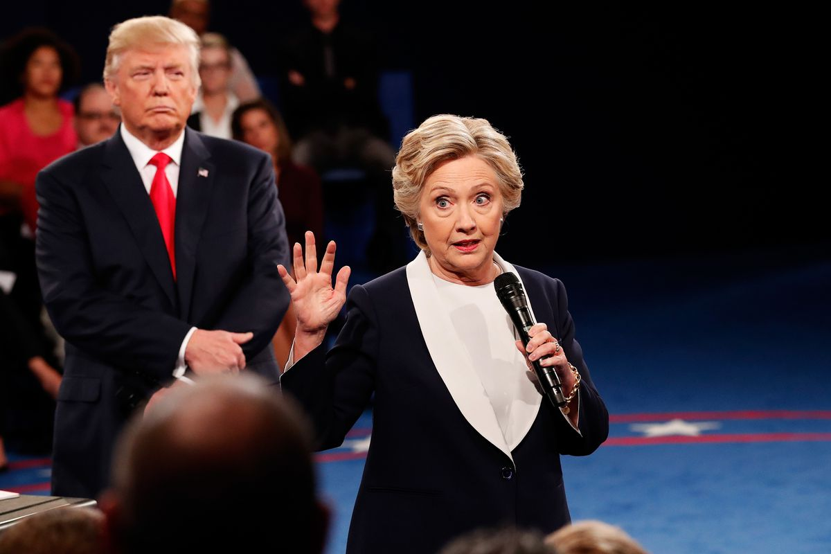 Hillary Clinton speaks as Republican presidential nominee Donald Trump listens during the town hall debate at Washington University