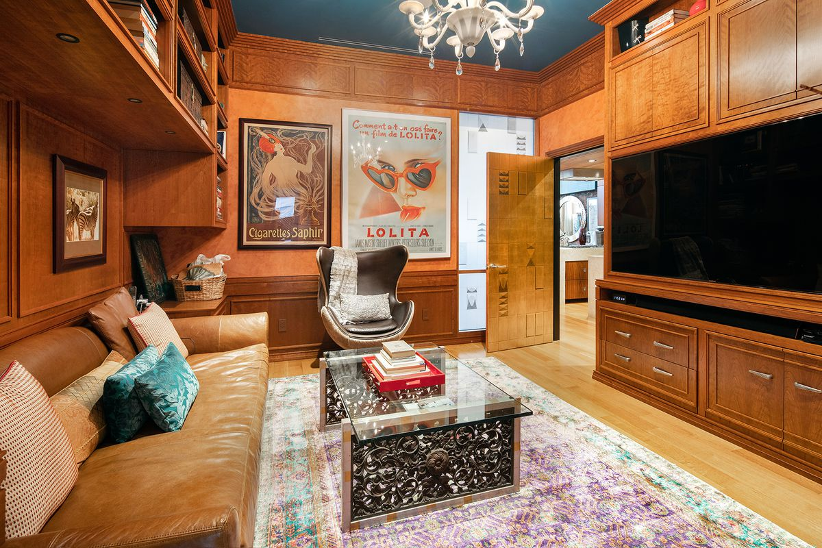 A library with built-in wooden furniture, a glass coffee table, and a leather brown couch.