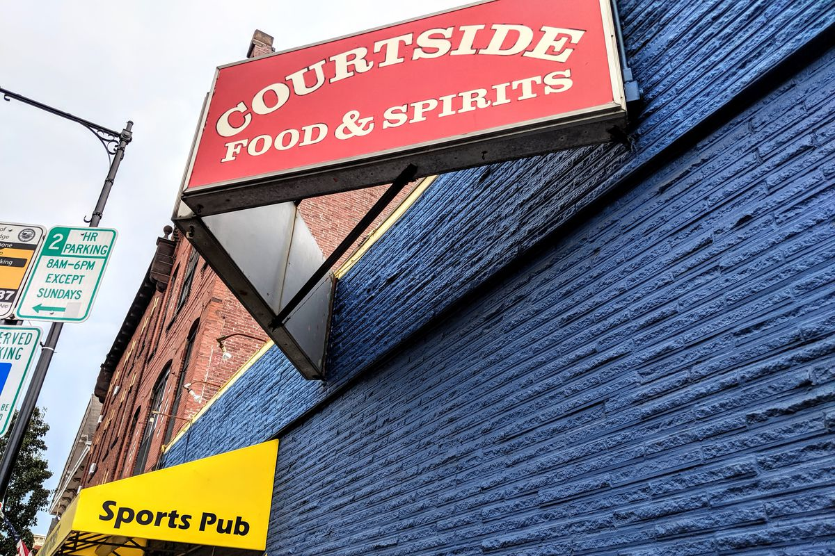 A blue-painted brick building with yellow awnings and a red sign that reads Courtside Food & Spirits