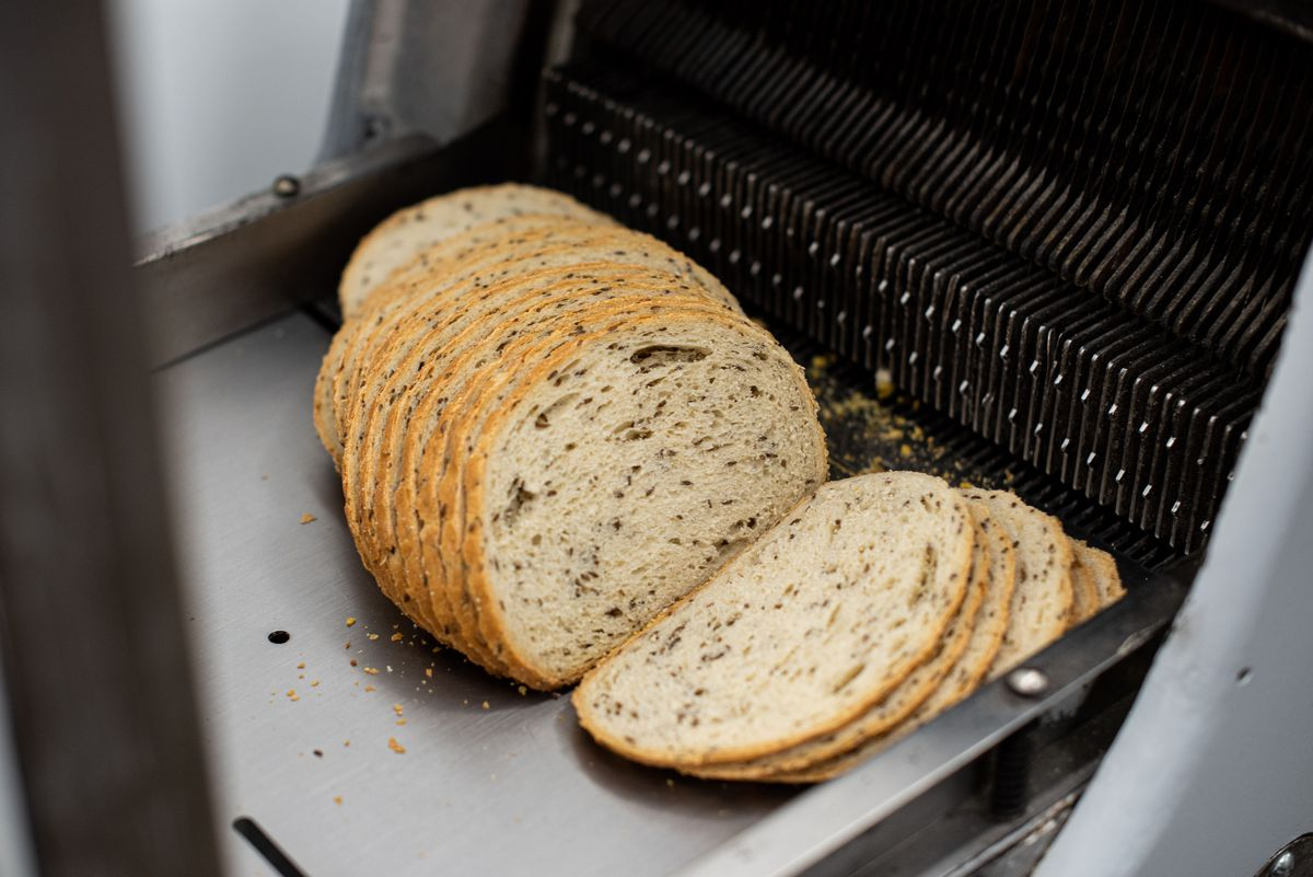A loaf of rye bread sits on the slicer, showing its seeded insides.
