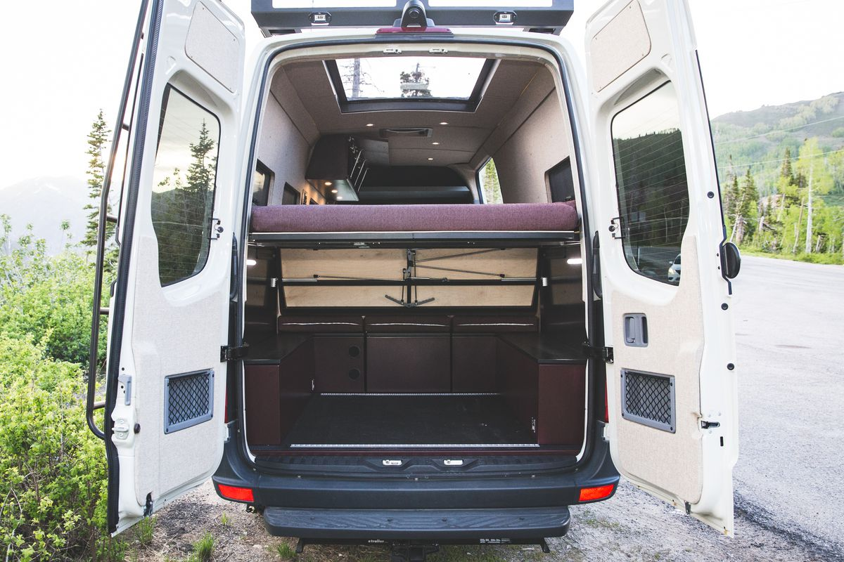 The rear of a Sprinter van features a gear garage, bed, and a large skylight.
