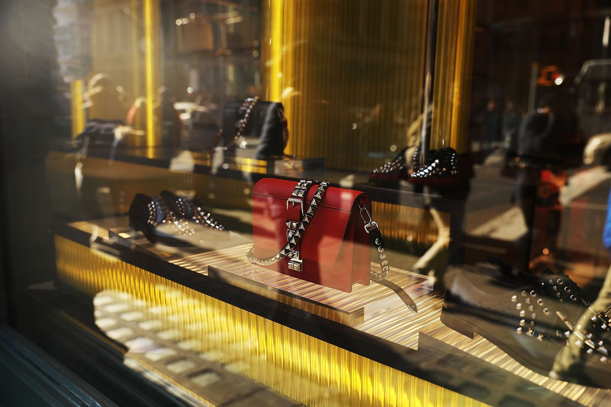A red studded bag sits behind glass.