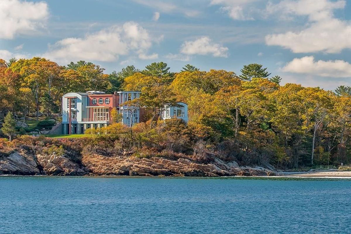 Postmodern home perches on ledge by the ocean.