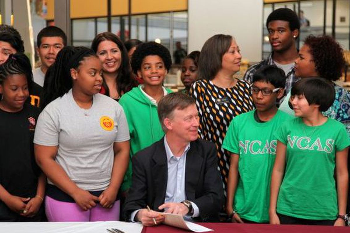 Gov. John Hickenlooper, surrounded by students from DCIS Montbello and NCAS - Noel Community Arts School, signs a bill changing Denver Public Schools' PERA contributions.