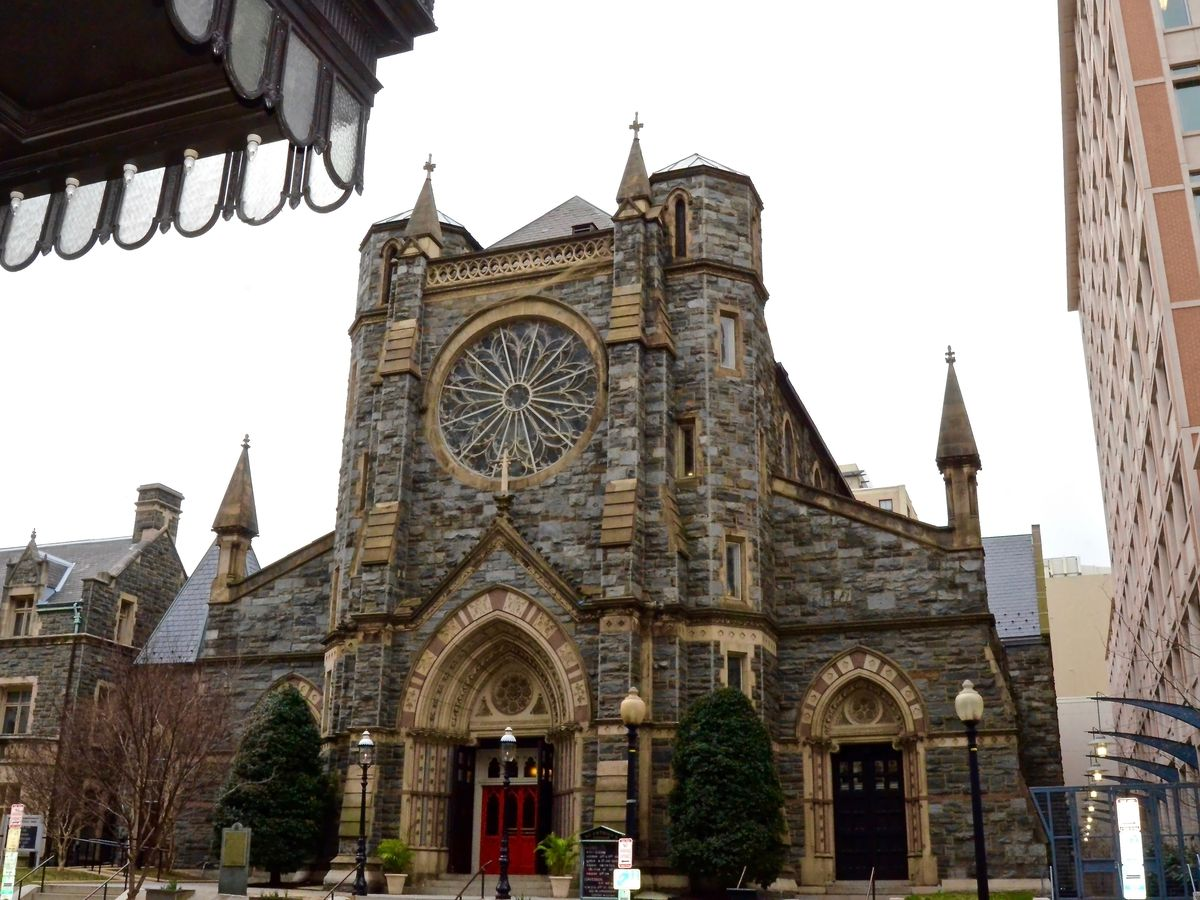 A stone church seen from across the street. The church has an English style and includes a Rose window.
