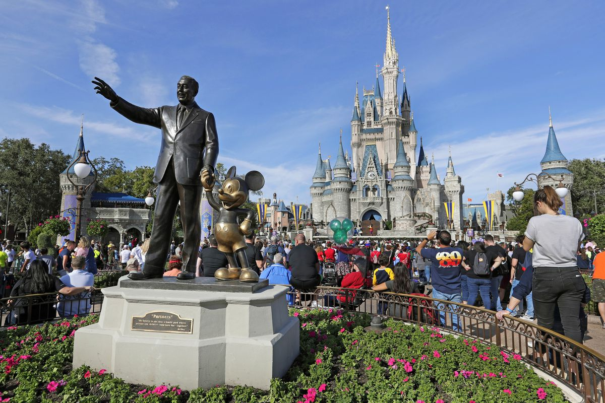 In this Wednesday, Jan. 9, 2019 photo, guests watch a show near a statue of Walt Disney and Micky Mouse in front of the Cinderella Castle at the Magic Kingdom at Walt Disney World in Lake Buena Vista, Fla.