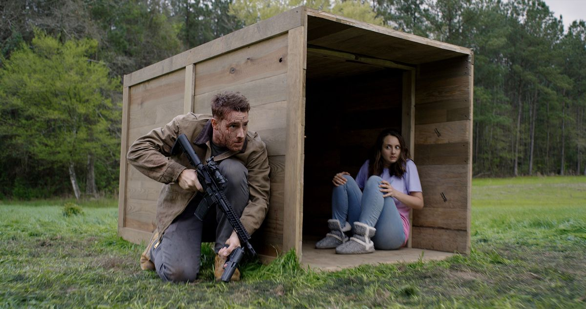 A scruffy-looking, bloody-faced man crouches behind a huge wooden crate and clings to a handgun and a rifle, while a frightened-looking woman in pastels sits inside the crate, staring in his direction.