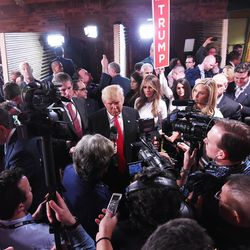 Republican presidential candidate Donald Trump with wife Melania Trump at right, speaks to the media in the spin room after the CBS News Republican presidential debate at the Peace Center, Saturday, Feb. 13, 2016, in Greenville, S.C.