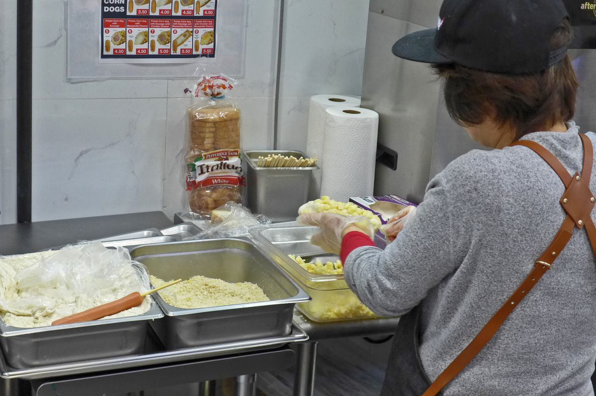 A figure in a black baseball cap and gray sweatshirt adds potato cubes to the exterior of a corn dog.
