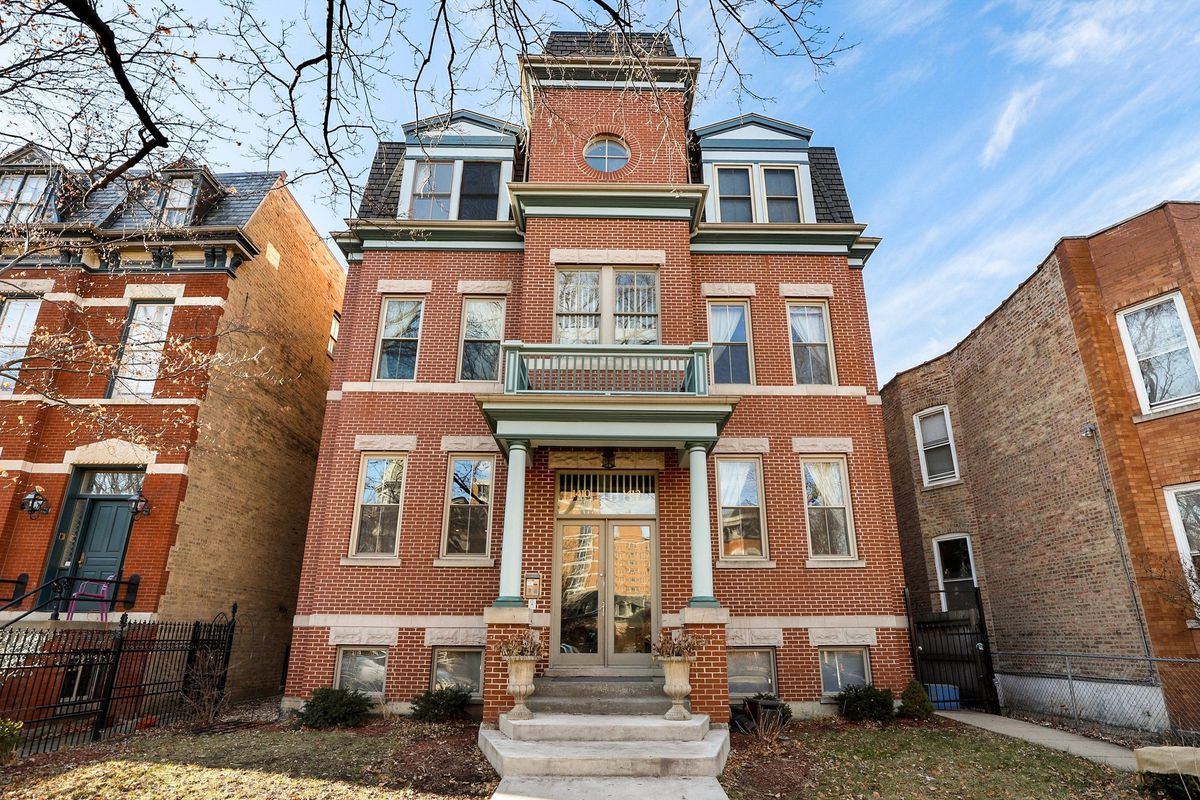 A three story brick home with columns around a glass door entrance. There is a front yard.