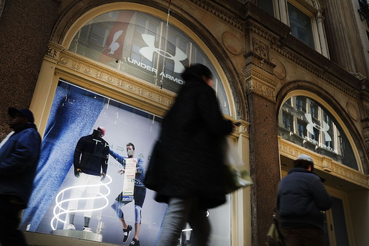 People in coats walk outside a storefront.