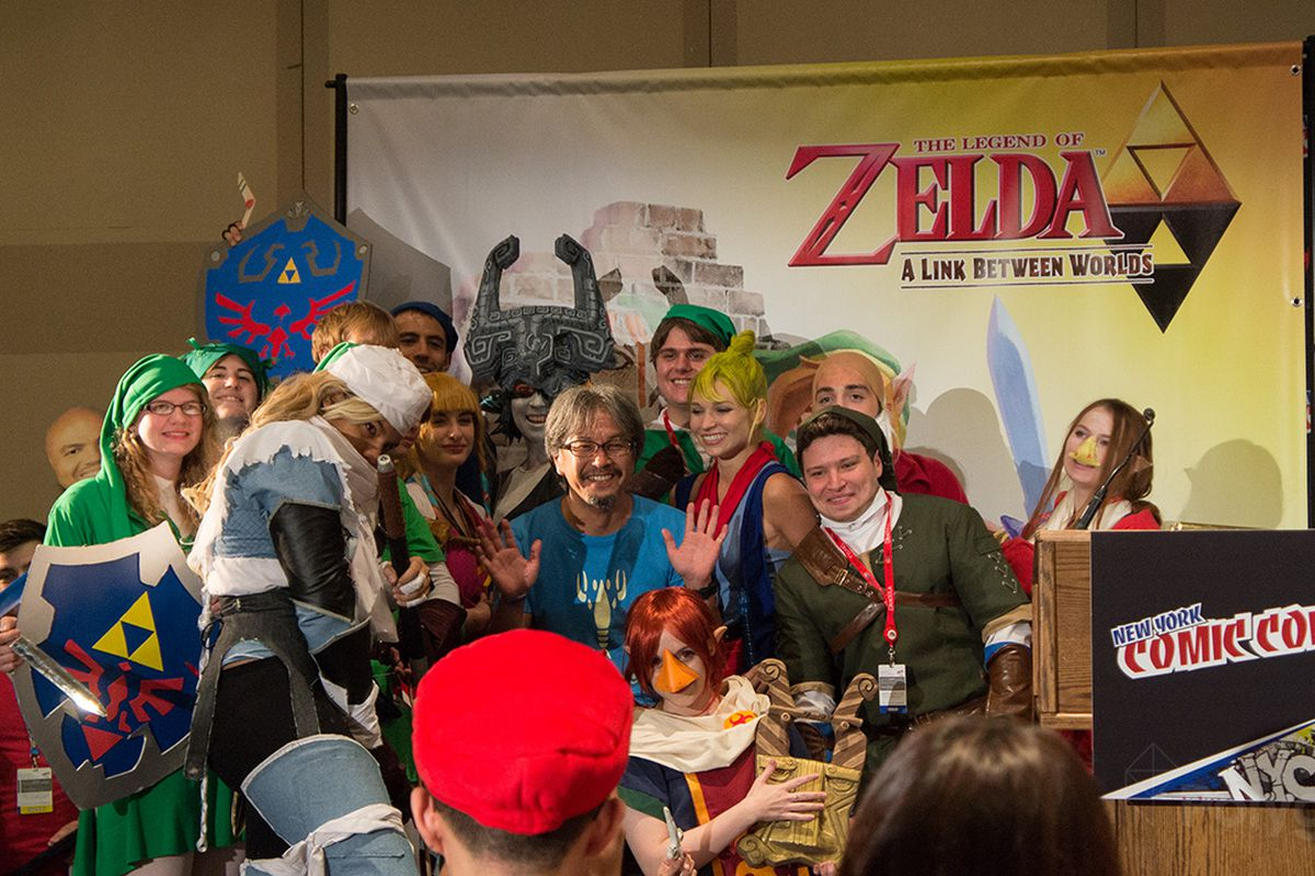 Eiji Aonuma surrounded by fans in Zelda cosplay at the New York Comic Con 2013 panel for The Legend of Zelda: A Link Between Worlds