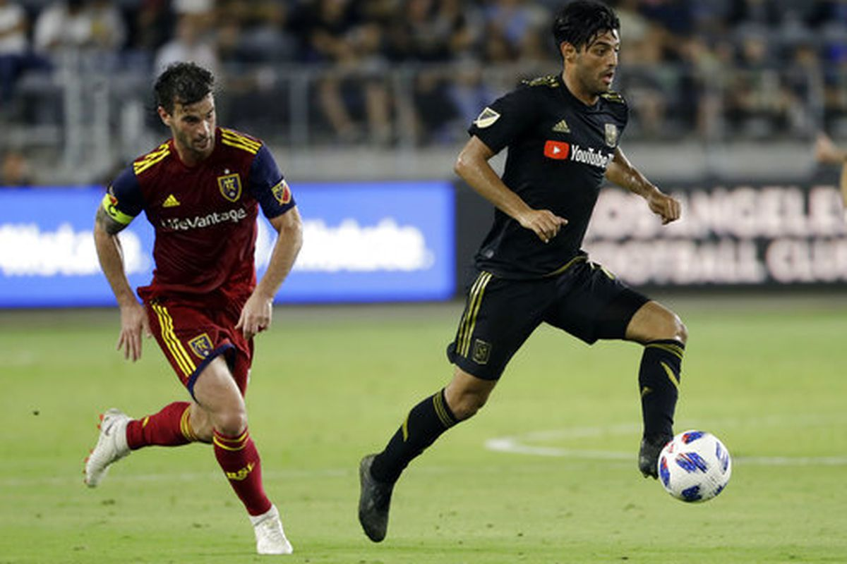 Los Angeles FC forward Carlos Vela, right, controls the ball in front of Real Salt Lake midfielder Kyle Beckerman during the second half of an MLS soccer match Wednesday, Aug. 15, 2018, in Los Angeles. (AP Photo/Marcio Jose Sanchez)