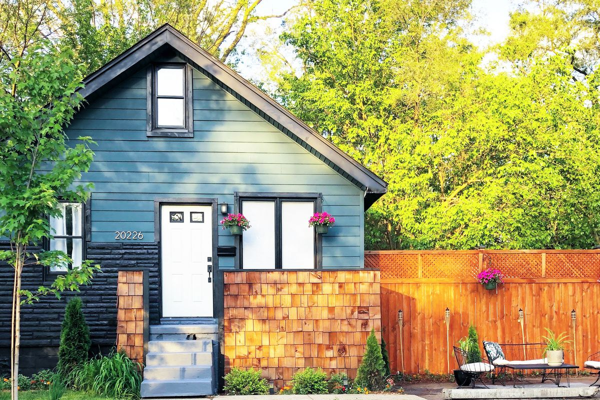 A tiny two-story home with blue vinyl and cedar shake siding. To the right of the house, a lounge area with tiki torches sits in front of a wood fence.