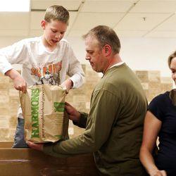 Justin Petersen helps his son, Brenden, 11, lift a bag of groceries at the Utah Food Bank.