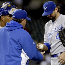 Kansas City Royals starting pitcher Luke Hochevar, right, hands manager Ned Yost the ball against the Detroit Tigers in the eighth inning of a baseball game in Detroit, Monday, Sept. 24, 2012.