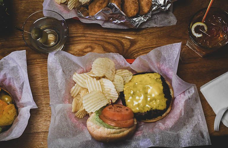 A cheeseburger in a red basket with parchment paper, and potato chips surrounded by cocktails.
