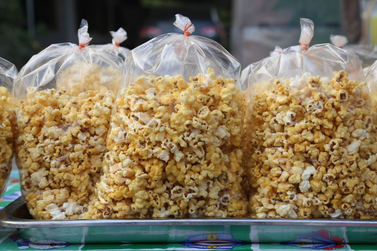 Bulk popcorn in sealed plastic bags on a metal tray.