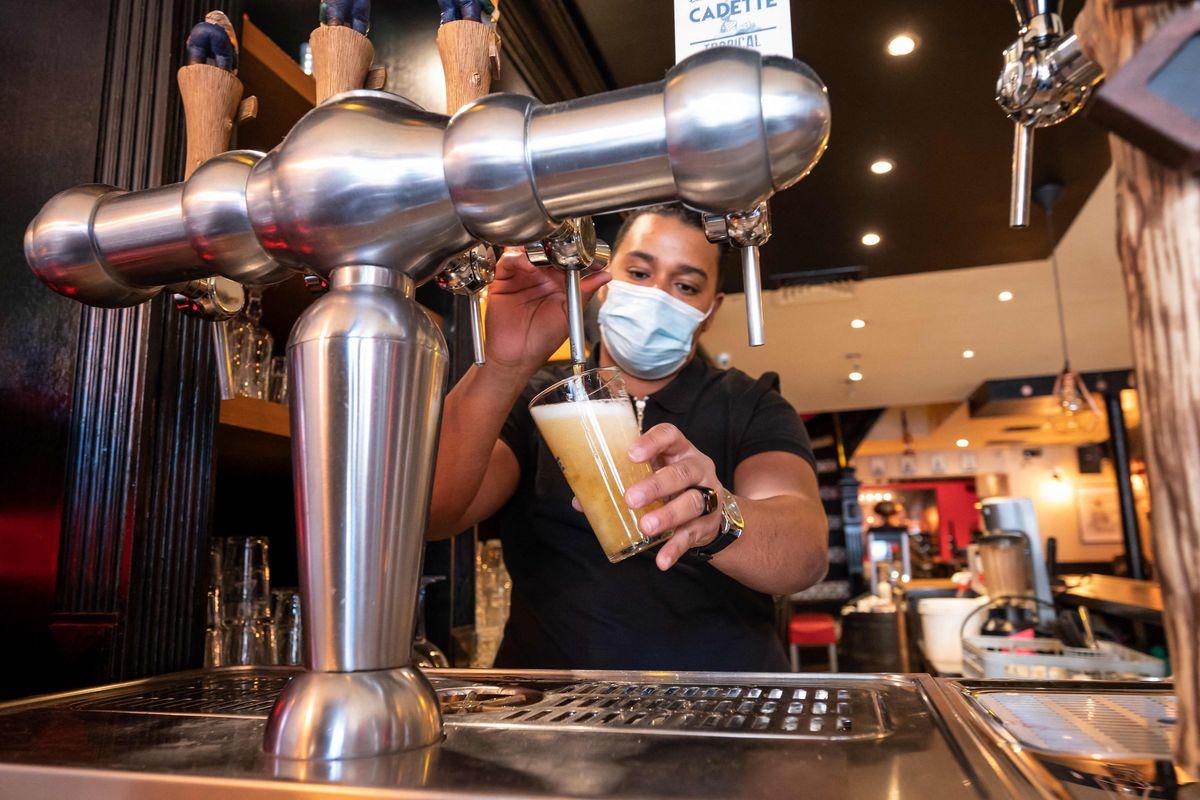 A restaurant owner tests the beer pump in his restaurant in Paris last week.