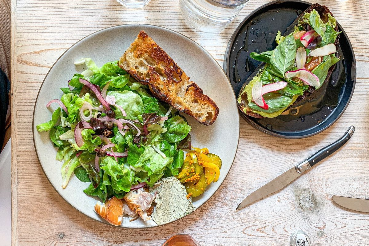 A top-down view of salad with grilled bread and a fancy toast.