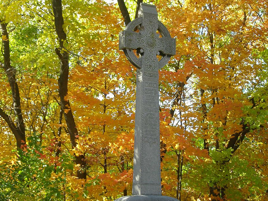A gravesite with a tall stone cross. The gravesite is surrounded by colorful autumn leaves.