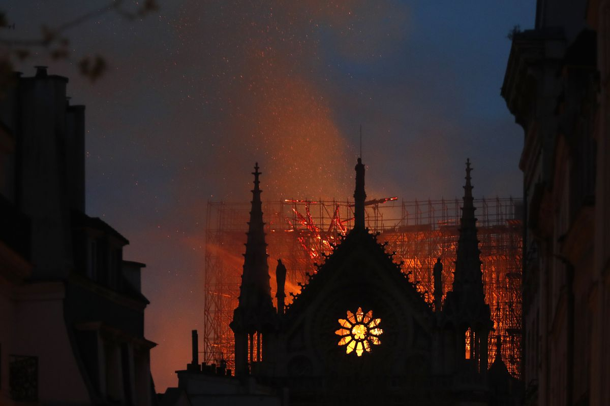 Flames and smoke rise from Notre Dame cathedral as it burns in Paris, Monday. Massive plumes of yellow brown smoke is filling the air above Notre Dame Cathedral and ash is falling on tourists and others around the island that marks the center of Paris.