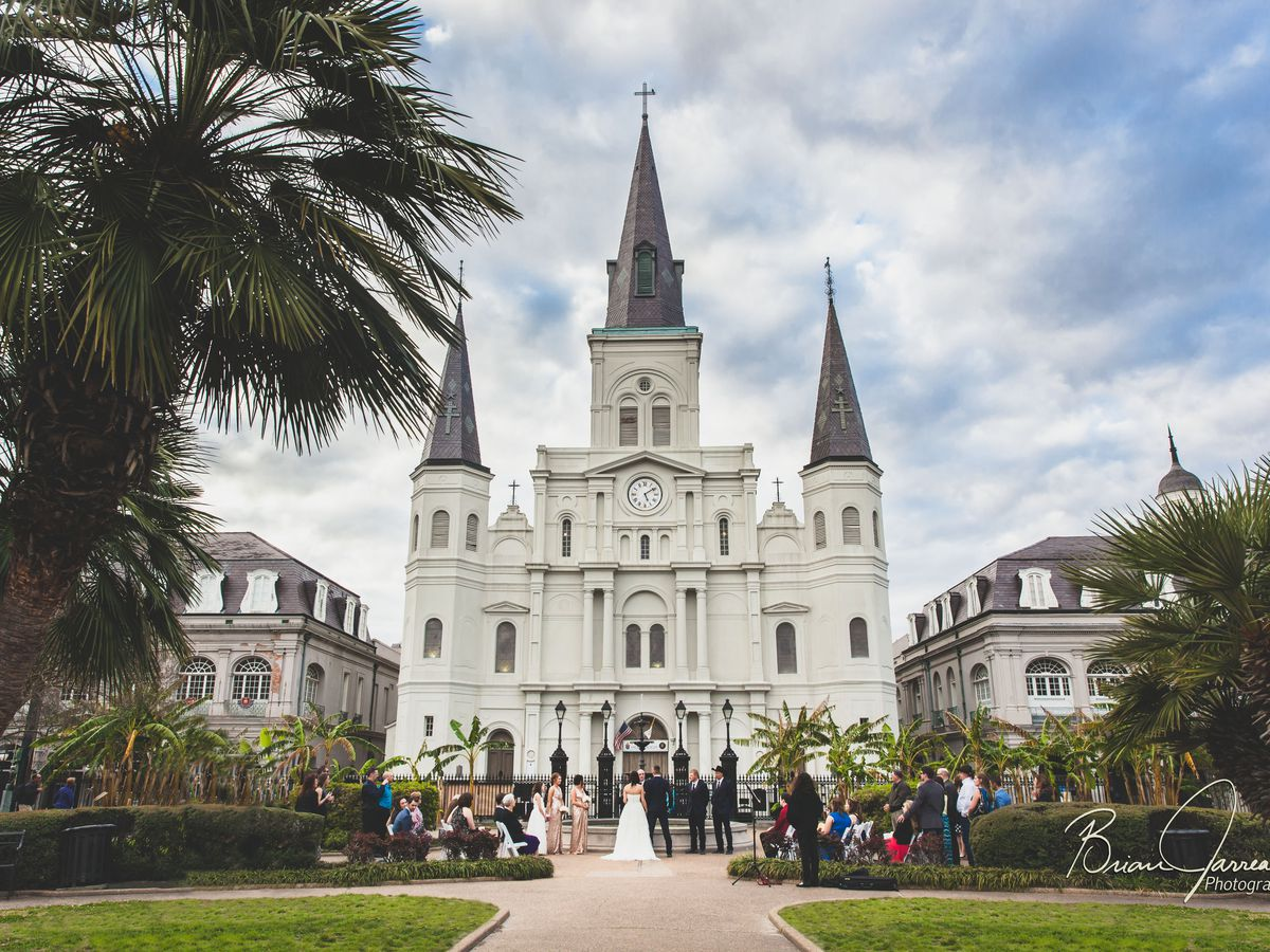 The exterior of Jackson Square in New Orleans. The facade is white and there are three dark grey towers.