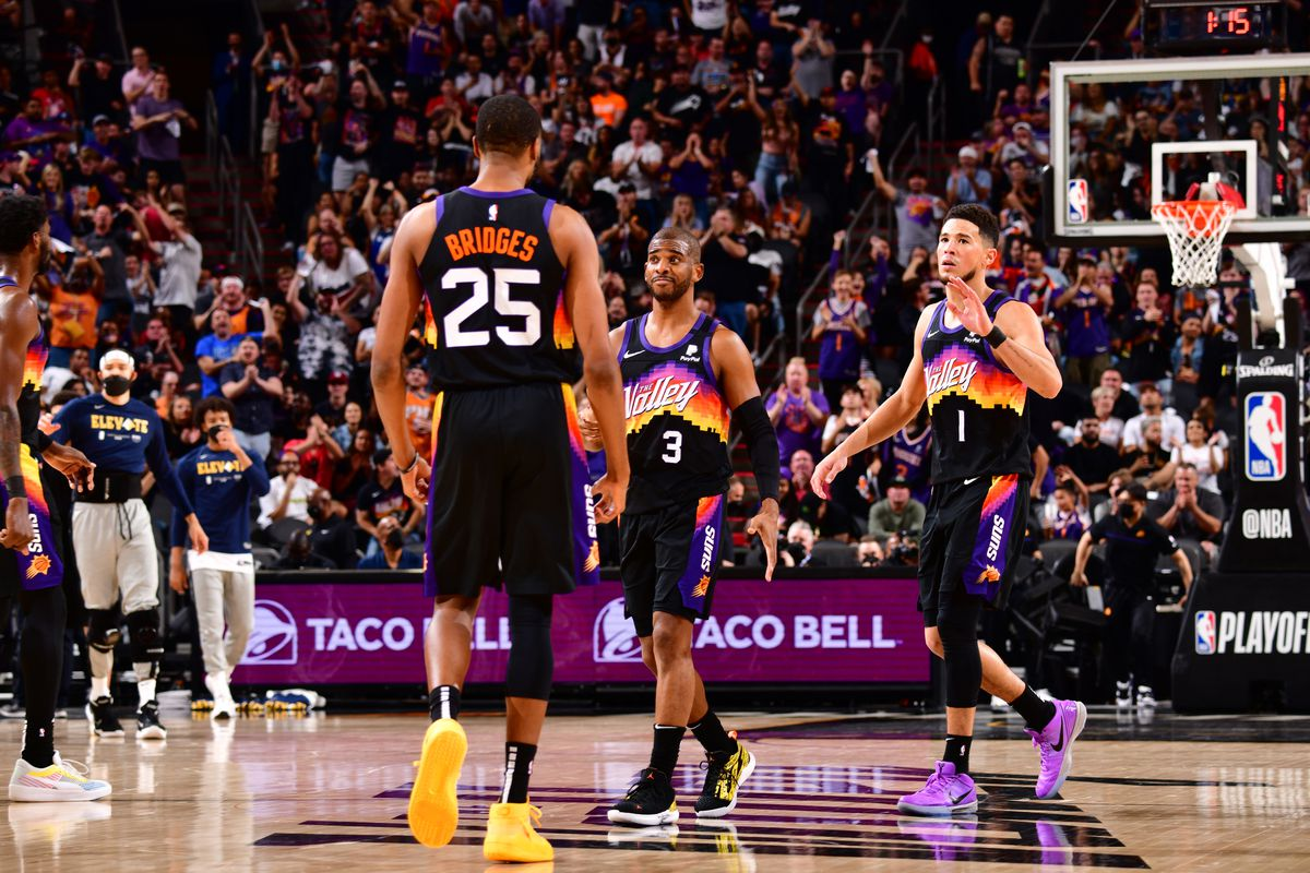 Mikal Bridges celebrates with Chris Paul and Devin Booker of the Phoenix Suns during Round 2, Game 1 of the 2021 NBA Playoffs on June 7, 2021 at Phoenix Suns Arena in Phoenix, Arizona.