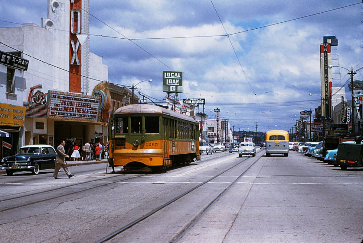 A man crosses the street in front of an old black car and a streetcar