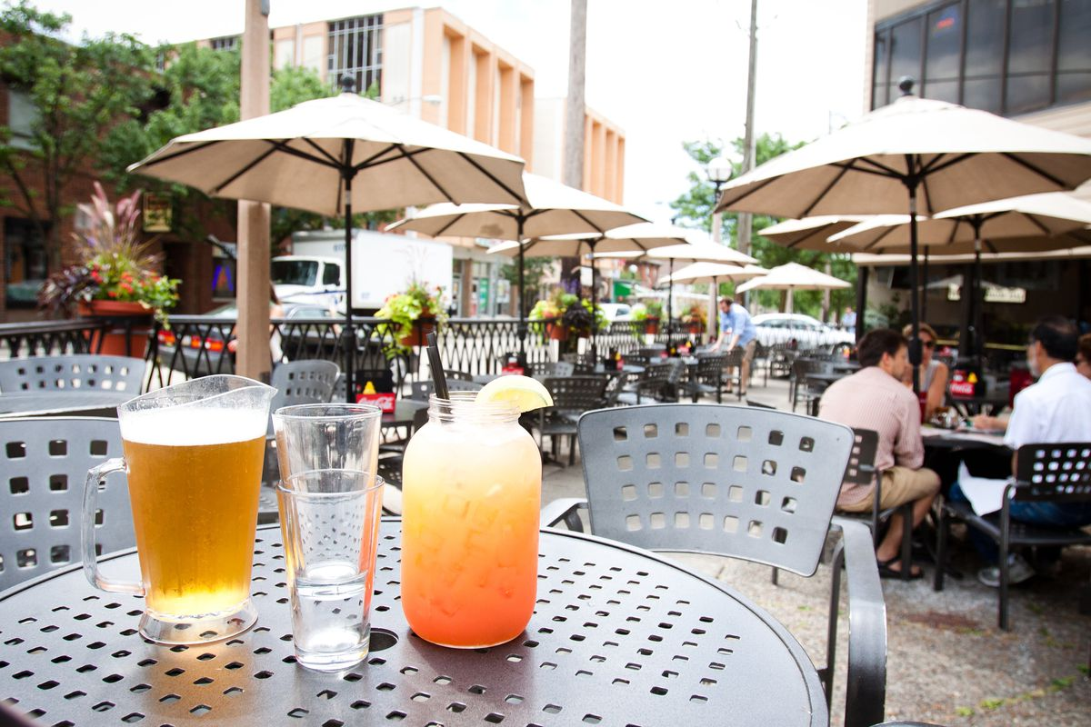 a pitcher of beer and a large jar of orange and yellow colored cocktail with two beer glasses on a black metal patio table