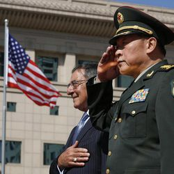 U.S. Defense Secretary Leon Panetta, left, stands at attention next to China's Defense Minister Liang Guanglie at the Bayi Building in Beijing, China Tuesday, Sept. 18, 2012.