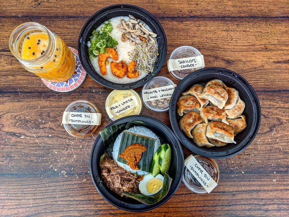 Overhead view of a spread of takeout Malaysian dishes on a wooden table