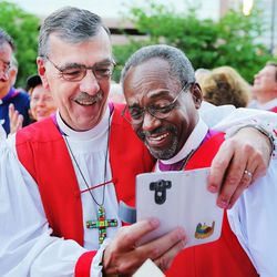 Bishop Thomas Ely, of Vermont, takes a photo with Presiding Bishop-elect Michael Curry, of North Carolina, during a rally against gun violence Sunday, June 28, 2015, from the Salt Palace Convention Center to Pioneer Park and back in Salt Lake City.