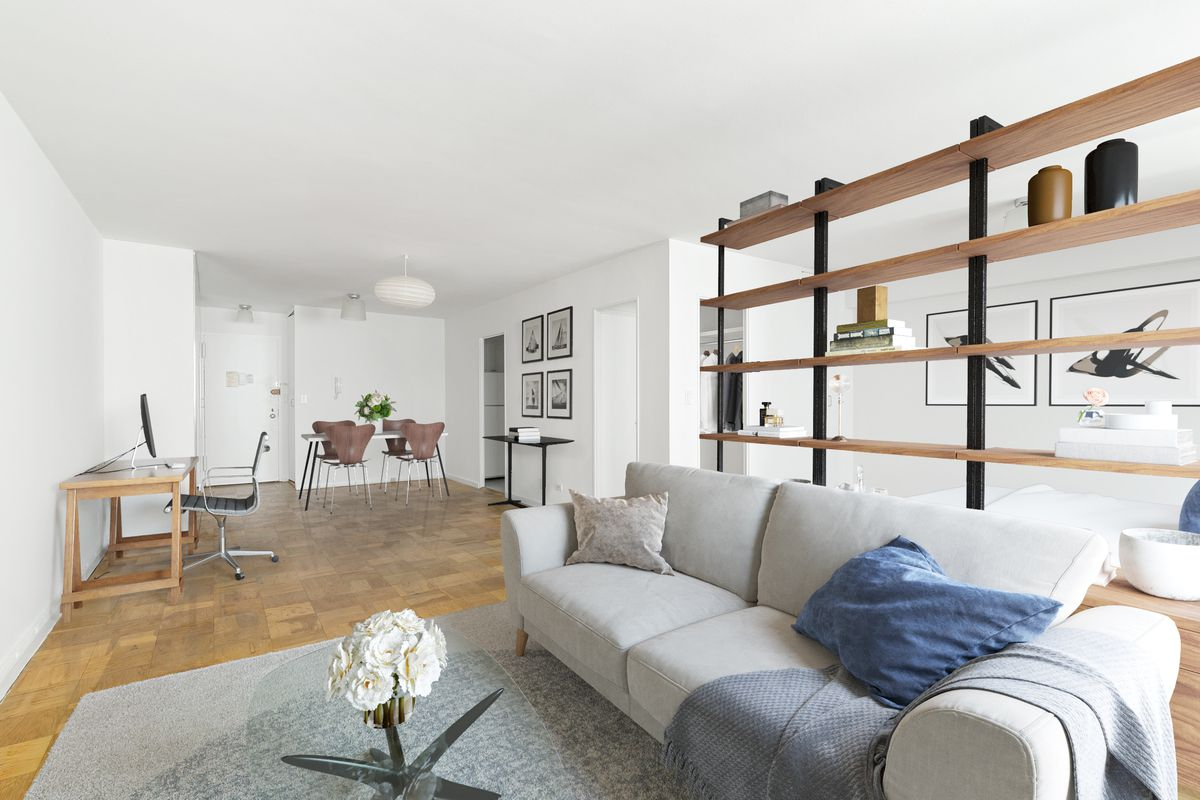 A living room with a grey couch, a grey rug, hardwood floors, and a round glass coffee table.