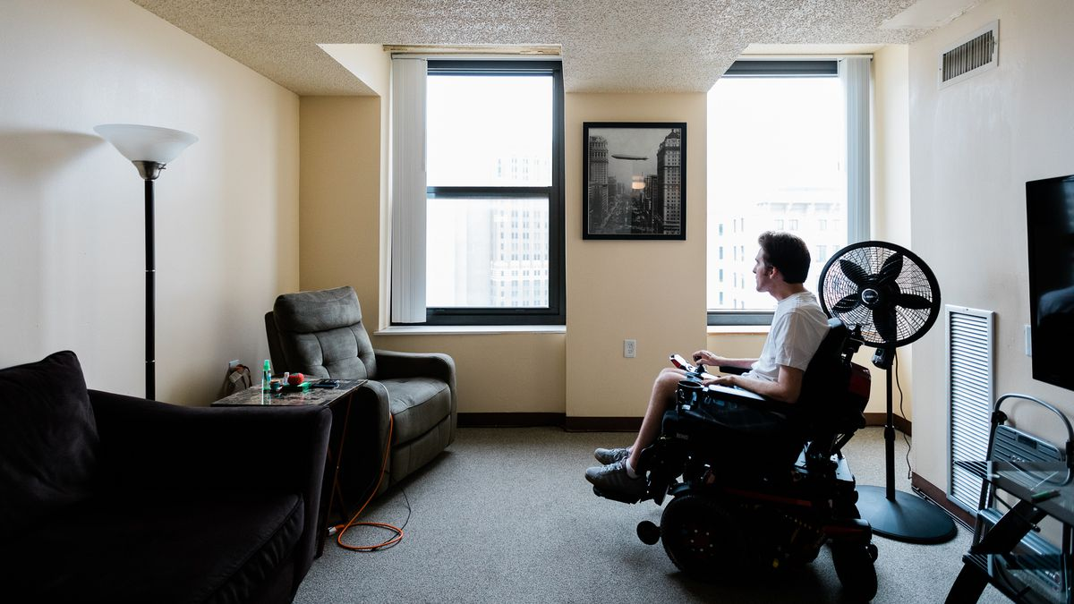 A man in an electric wheelchair sits by a window in an apartment living room. There's two recliners and a lamp on one side, a fan and TV on the other.