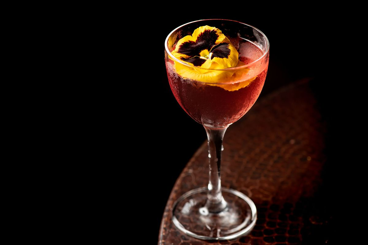 Red cocktail in a glass with yellow flower with a dark background.