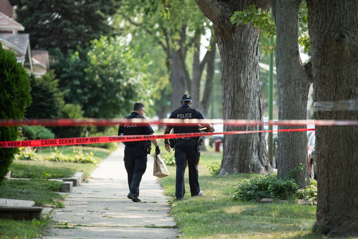 Officers walk in the 8000 block of South Bennett Avenue in the South Chicago neighborhood, where a 12-year-old boy was fatally shot, Saturday afternoon, Sept. 11, 2021. | Pat Nabong/Sun-Times