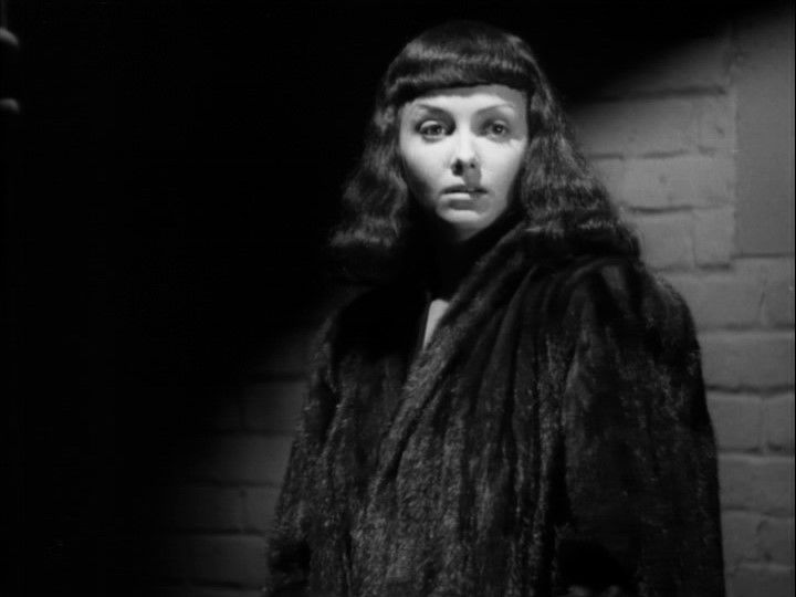 a woman in a large fur coat stands against a brick wall, in a movie shot in black and white