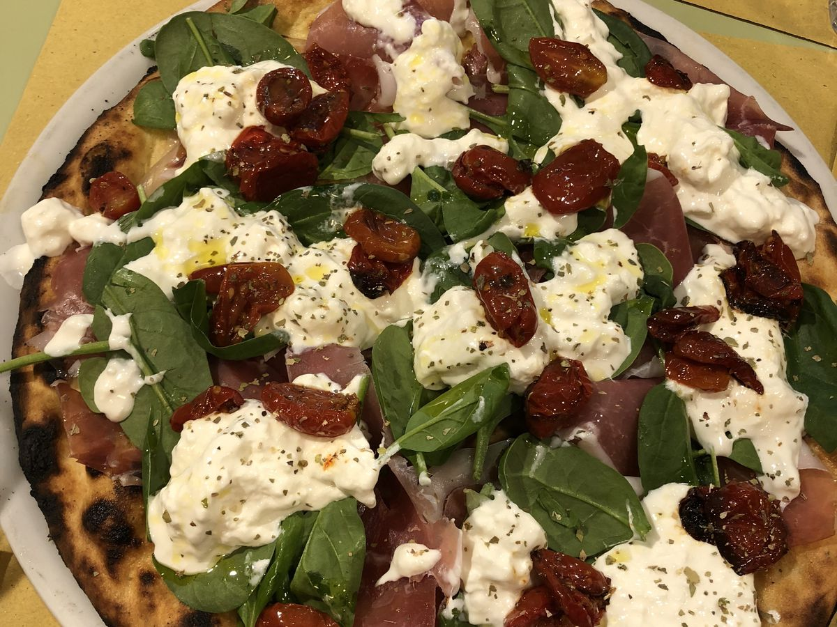 A full pizza with huge hunks of cheese, tomatoes, prosciutto, and basil