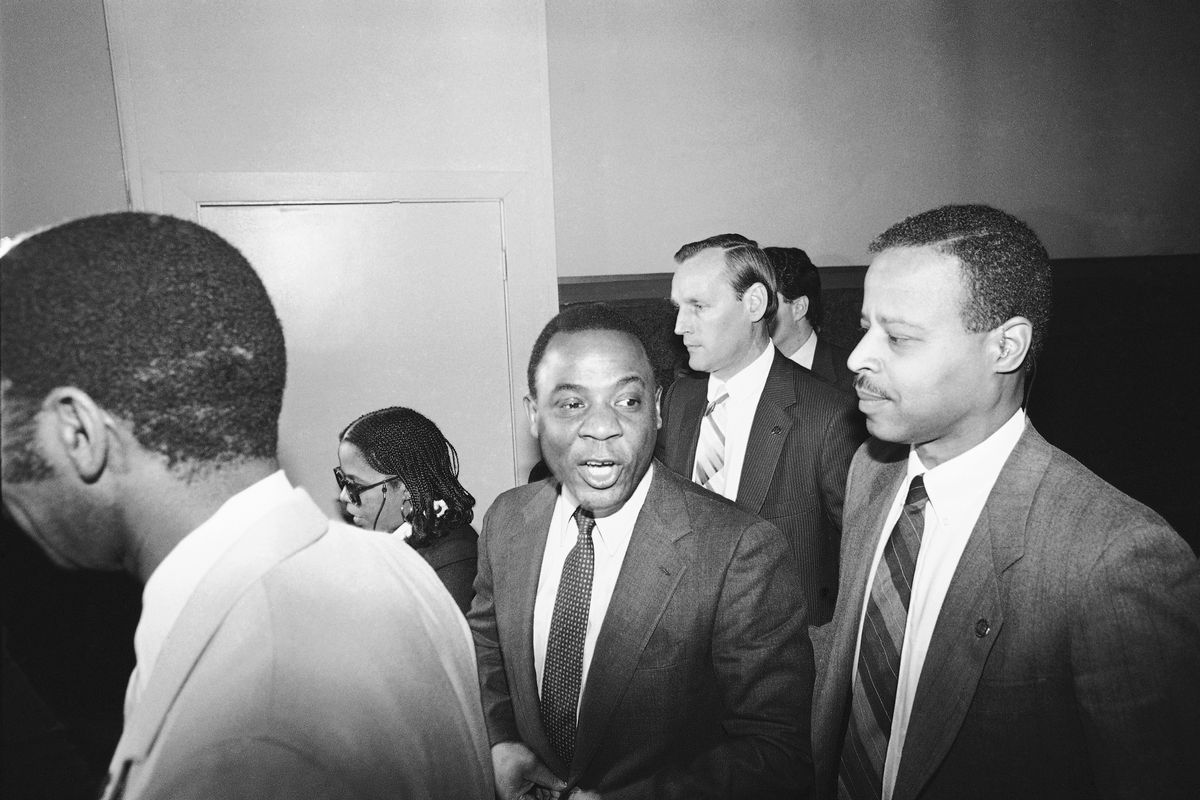 Mayor W. Wilson Goode, center, leaves court after testifying at the trial of MOVE member, Ramona Africa, on January 25, 1986.