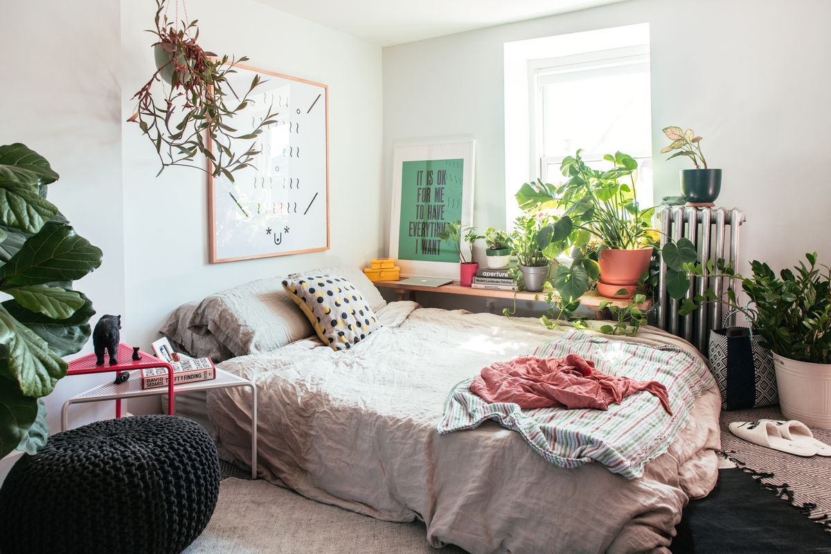A bedroom. There is a bed with pillows and throw blankets. There are multiple houseplants on a desk by a window. There are multiple framed works of art hanging in the room. There is a pair of slippers next to the bed on the floor.