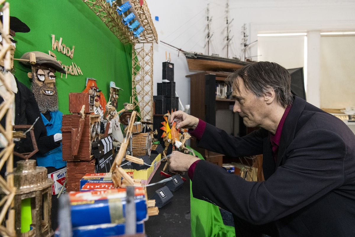"""Wayne Kusy, toothpick modeler, adjusts one of his models he made for his music video """"I Think There For I Am"""" in his living room turned stop motion set,"""