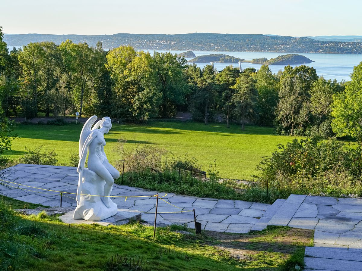 A sculpture in white marble sits on a stone patio surrounded by green grass and trees. In the distance you can see the fjord waters and various islands.