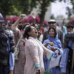 Pakistani riot policemen stand guard, as a supporter of Prime Minister Yousuf Raza Gilani, center, shouts slogans in Gilani's support, outside the Supreme court  in Islamabad, Pakistan, Thursday, April 26, 2012. The Supreme Court convicted Gilani of contempt on Thursday for refusing to reopen an old corruption case against President Asif Ali Zardari , but spared him a prison term in a case that has stoked political tensions in the country. (AP Photo/Muhammed Muheisen)