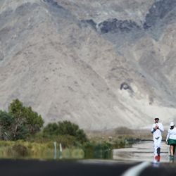 Iain Hughes (L) of Cincinnati, Ohio passes through heat waves on highway 136 north of Lake Owens as he approaches the town of Lone Pine during the AdventurCORPS Badwater 135
