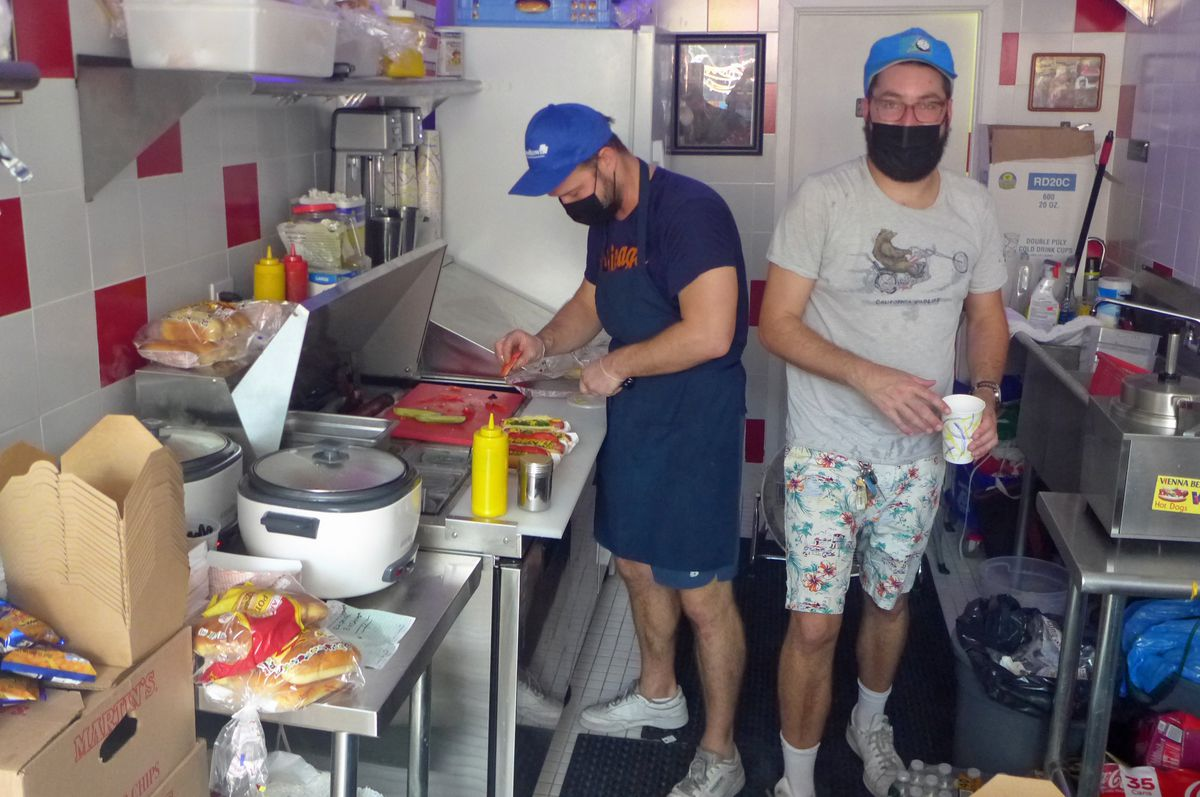 Two guys making hot dogs in a tiny kitchen, once looking at the camera.
