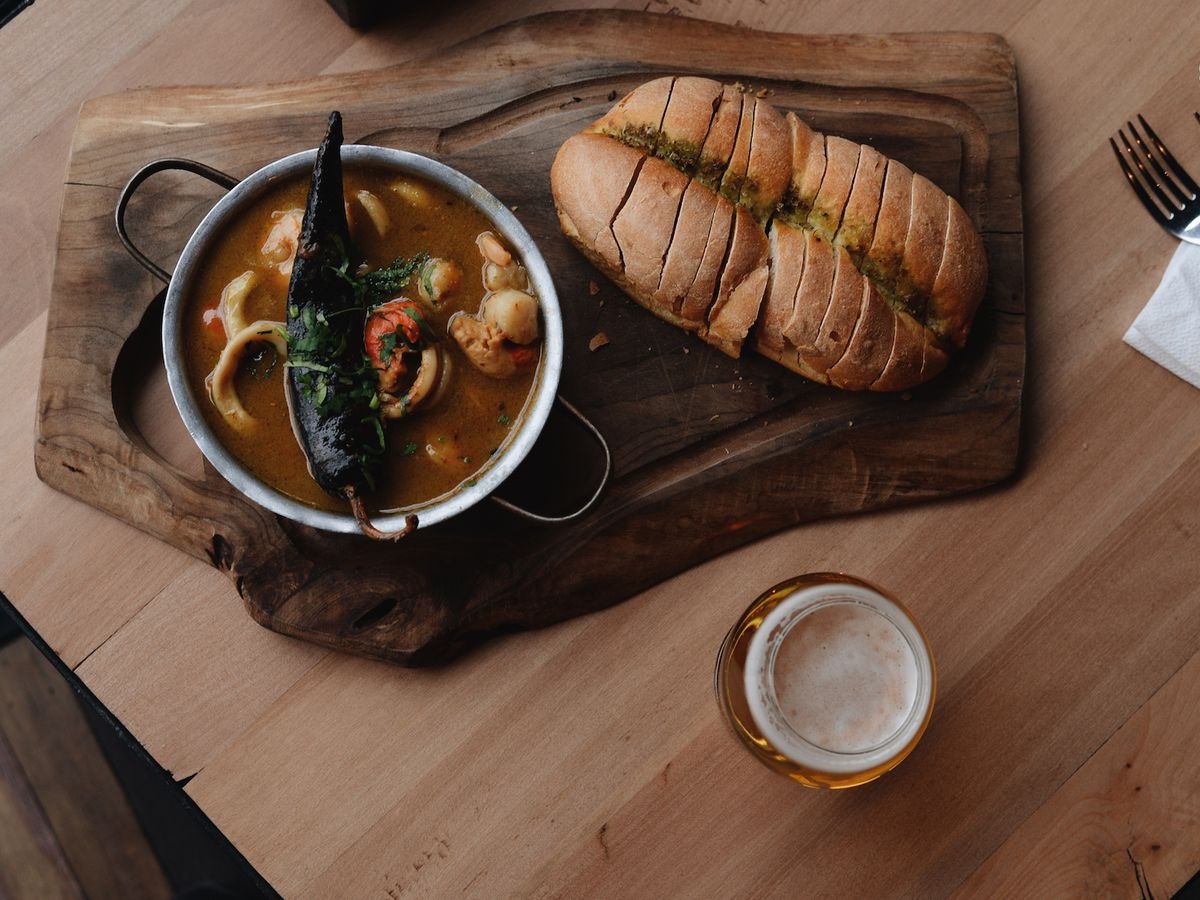 From above, a meat board resting on a wooden table beneath a bowl of stew dotted with seafood and veggies and topped with a large pepper resting across the rim, beside a loaf of bread streaked with sauce and cut into slices