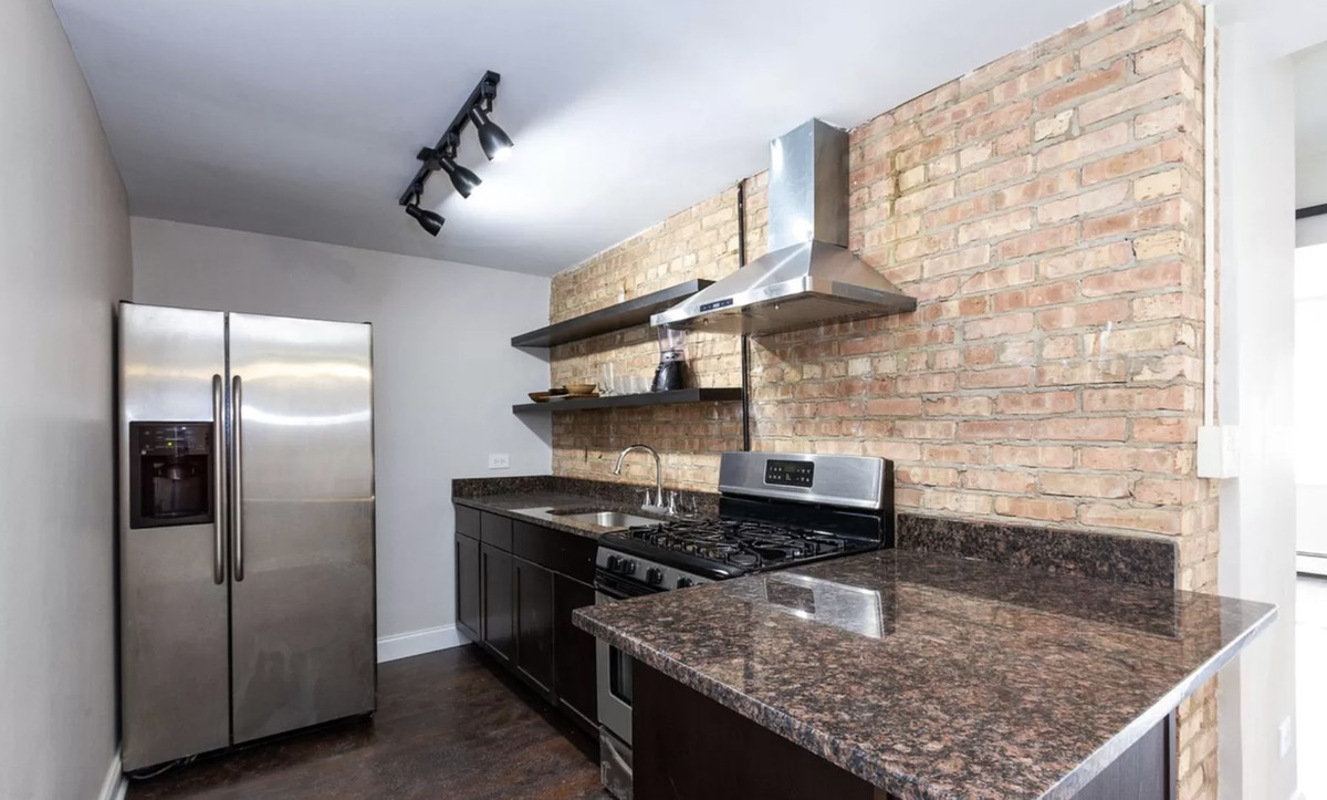 A kitchen with a granite countertop, stainless steel appliances, open shelving, and exposed brick.