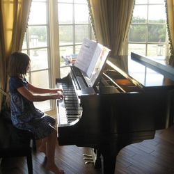 Emily McLaughlin, now 10, practicing piano while on vacation in July 2011.