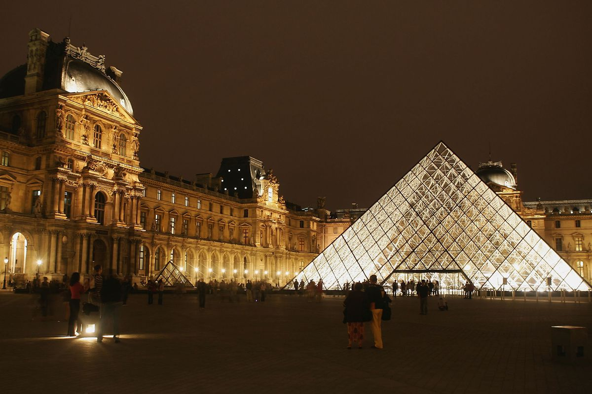 A glass and steel pyramid at night set among the courtyard of opulent French buildings.